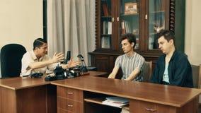 Productor cinematográfico en hablar enojado de la red de pelo con los trabajadores de la oficina sobre el guión almacen de video