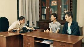 Productor de película en hablar enojado de la camisa blanca con los trabajadores de la oficina sobre el guión almacen de video