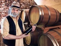 Productor del vino que muestra su botella de vino delante del barriq Fotografía de archivo libre de regalías
