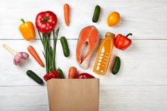 Productos alimenticios útiles en el bio bolso de papel en fondo de madera fotografía de archivo libre de regalías