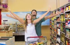 Productos alimenticios de compra de los pares brillantes felices Foto de archivo