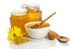 Productos amarillos miel, polen de la flor y de la abeja en blanco Imagen de archivo