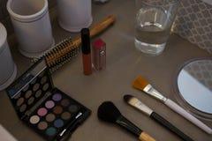 Productos de belleza con el vidrio de consumición en la tabla Fotos de archivo libres de regalías