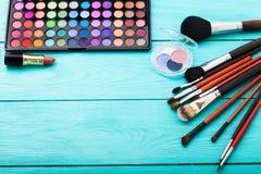 Productos de belleza para el maquillaje Sombras, cepillos Cosméticos en fondo de madera azul Visión superior Foco selectivo Copie Imagen de archivo