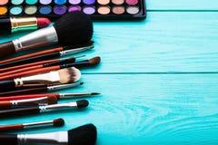 Productos de belleza para el maquillaje Sombras, cepillos Cosméticos en fondo de madera azul Visión superior Foco selectivo Copie Imágenes de archivo libres de regalías