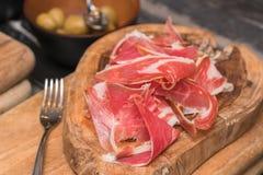 Productos de carne fría procesados, en una tabla de cortar de madera Fotografía de archivo