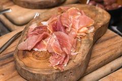 Productos de carne fría procesados, en una tabla de cortar de madera Foto de archivo