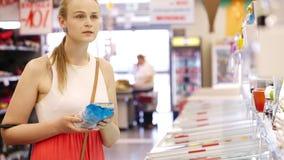 Productos de compra de la mujer joven en el supermercado metrajes