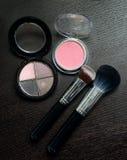 Productos de los cosméticos del maquillaje en fondo negro de madera Imagen de archivo