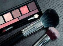 Productos de los cosméticos del maquillaje en fondo negro de madera Fotos de archivo