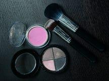 Productos de los cosméticos del maquillaje en fondo negro de madera Fotos de archivo libres de regalías