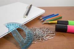 Productos de los efectos de escritorio, marcadores, corchetes, lápices y un ordenador portátil Imagen de archivo libre de regalías