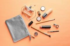 Productos de maquillaje con el bolso cosmético en fondo del color fotos de archivo