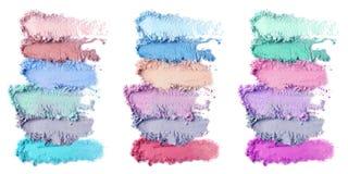 Productos de maquillaje machacados en el fondo blanco Sistema de color de sombras de ojos imagen de archivo