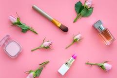 Productos de maquillaje para las chicas jóvenes Composición con los cosméticos con tonos color de rosa Barra de labios, bulto, so imagen de archivo