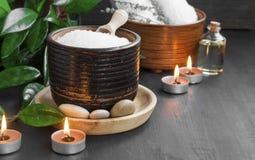 Productos del balneario con la sal de baño, el aceite de baño, las piedras del masaje y la vela fotografía de archivo libre de regalías