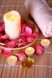 Productos del balneario con los pétalos color de rosa, petróleo, toalla fotos de archivo