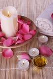 Productos del balneario con los pétalos color de rosa, petróleo, toalla imagen de archivo
