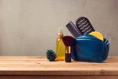 Productos del cuidado y de belleza del cuerpo en la tabla de madera sobre fondo gris Fotografía de archivo libre de regalías