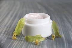 Productos naturales de los cosméticos - crema facial del tilo en fondo gris fotografía de archivo