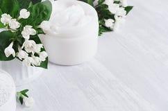 Productos orgánicos de los cosméticos del balneario de la primavera fresca con las pequeñas flores blancas y hojas del verde en e fotos de archivo