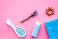 Productos para el cuidado de la piel para los niños con lavanda Botella, sal del balneario, toalla y juguete en copyspace rosado  Imagen de archivo libre de regalías
