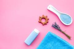 Productos para el cuidado de la piel para los niños con lavanda Botella, sal del balneario, toalla y juguete en copyspace rosado  Fotografía de archivo