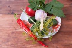 Productos para el hogar que conserva en la placa Pepinos, tomates, pimientas, ajo, las hojas de la pasa roja Fotos de archivo