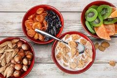 Productos para los cuencos de madera del desayuno sano con las nueces, frutas secadas El cereal forma escamas con leche Imagen de archivo libre de regalías