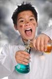 Productos químicos de mezcla del científico enojado joven Imagen de archivo libre de regalías