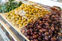Productos respetuosos del medio ambiente en una parada del mercado Diversas variedades de aceitunas conservadas en vinagre Foto de archivo