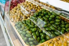 Productos respetuosos del medio ambiente en una parada del mercado Diversas variedades de aceitunas conservadas en vinagre Imagen de archivo