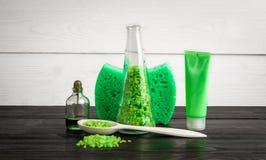 Productos verdes del tratamiento de la belleza de la composición en colores verdes: champú, jabón, sal de baño, aceite Imágenes de archivo libres de regalías