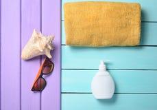 Productos y accesorios para relajarse en la playa: sunblock, toalla, gafas de sol, cáscara en un fondo de madera de la turquesa Fotos de archivo