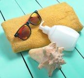Productos y accesorios para relajarse en la playa: sunblock, toalla, gafas de sol, cáscara en un fondo de madera de la turquesa Foto de archivo libre de regalías