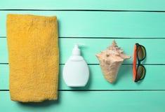Productos y accesorios para relajarse en la playa: sunblock, toalla, gafas de sol, cáscara en un fondo de madera de la turquesa Imagen de archivo