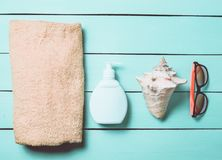 Products and accessories for relaxing on the beach: sunblock, towel, sunglasses, shell on a turquoise wooden background. The concept of the resort royalty free stock images