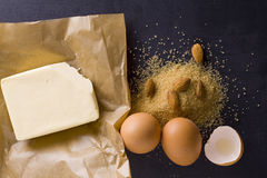 Products for baking. Baking ingredients eggs, brown sugar, almonds, butter on baking paper Stock Image