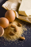 Products for baking. Baking ingredients eggs, brown sugar, almonds, butter on baking paper Stock Photos