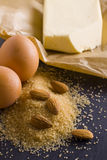 Products for baking. Baking ingredients eggs, brown sugar, almonds, butter on baking paper Stock Photography