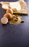 Products for baking. Baking ingredients eggs, brown sugar, almonds, butter on baking paper Royalty Free Stock Images