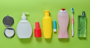 Products for beauty, self-care and hygiene on a green pastel background. Shampoo, perfume, lipstick, shower gel, toothbrush. Top view. Flat lay royalty free stock photos