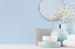 Products for body and skin care in light blue ceramic bowls, silver cosmetic bag, circle mirror and white flowers on wood table. stock image