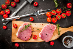 Products for cooking dinner. Fresh raw pork, steaks, on a cutting shale board on a black concrete table. With a hammer to beat the meat and a fork, with spices Royalty Free Stock Image