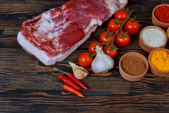 Products for cooking dinner. Fresh raw pork, steaks, on cutting shale board on a black table. Stock Photo
