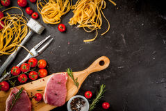Products for cooking dinner. Fresh raw pork, steaks, on cutting shale board on a black table. With hammer to beat meat and fork, with spices, fresh raw pasta Stock Photos