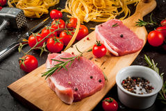 Products for cooking dinner. Fresh raw pork, steaks, on cutting shale board on a black table. With hammer to beat meat and fork, with spices, fresh raw pasta Stock Images