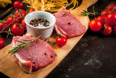 Products for cooking dinner. Fresh raw pork, steaks, on cutting shale board on a black table. With hammer to beat meat and fork, with spices, fresh raw pasta Stock Photo
