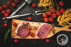 Products for cooking dinner. Preparations for cooking dinner. Fresh raw pork, steaks, on cutting shale board on a black table. With hammer to beat meat and fork Stock Photo