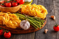 Products for cooking - fresh asparagus, pasta, olive oil. Royalty Free Stock Photo